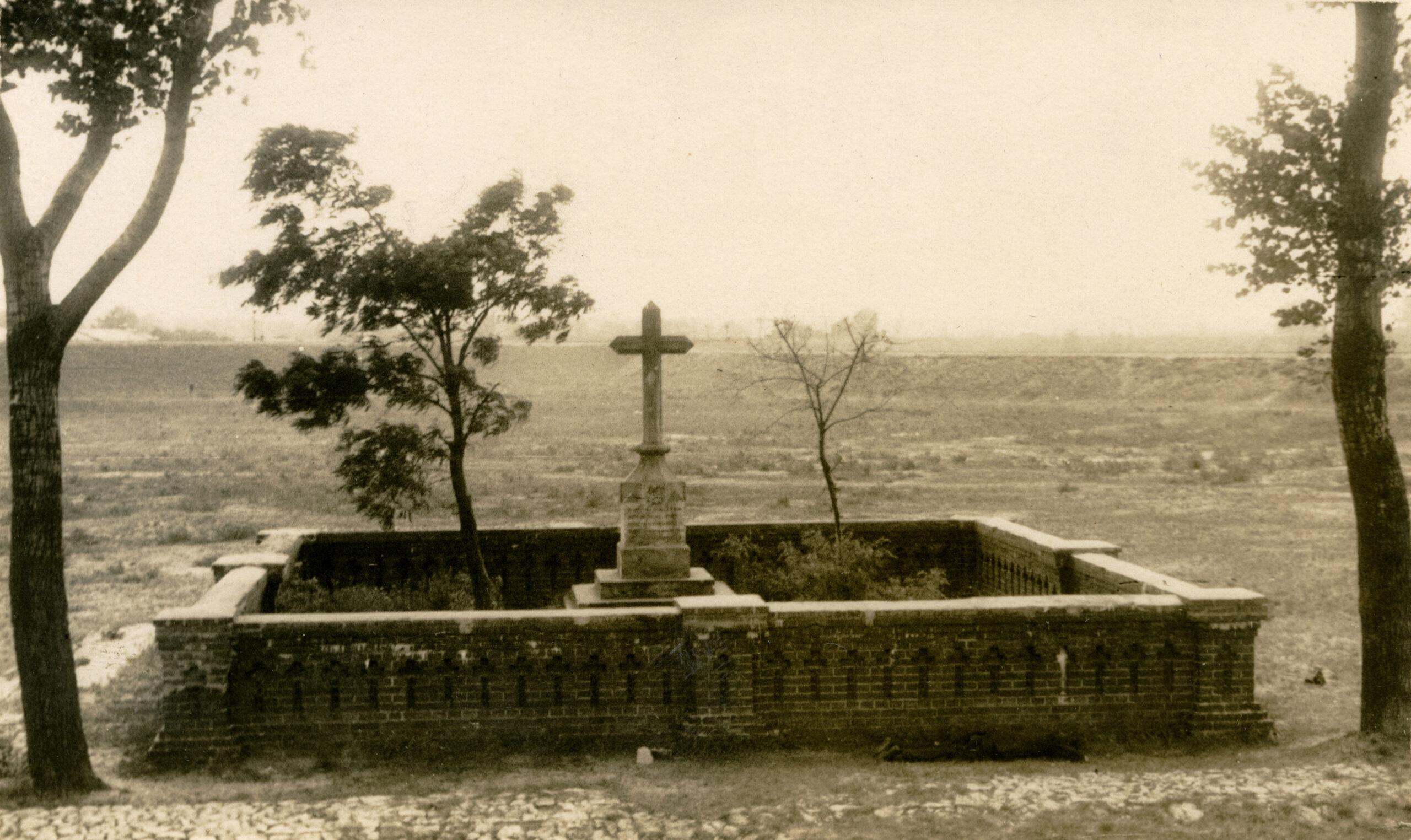 Czarno białe zdjęcie mogiły oznaczonej niskim murkiem i kamiennym krzyżem.