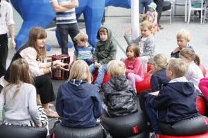 Lekcja muzealna na zewnątrz. Dzieci siedzące wokół edukatora.