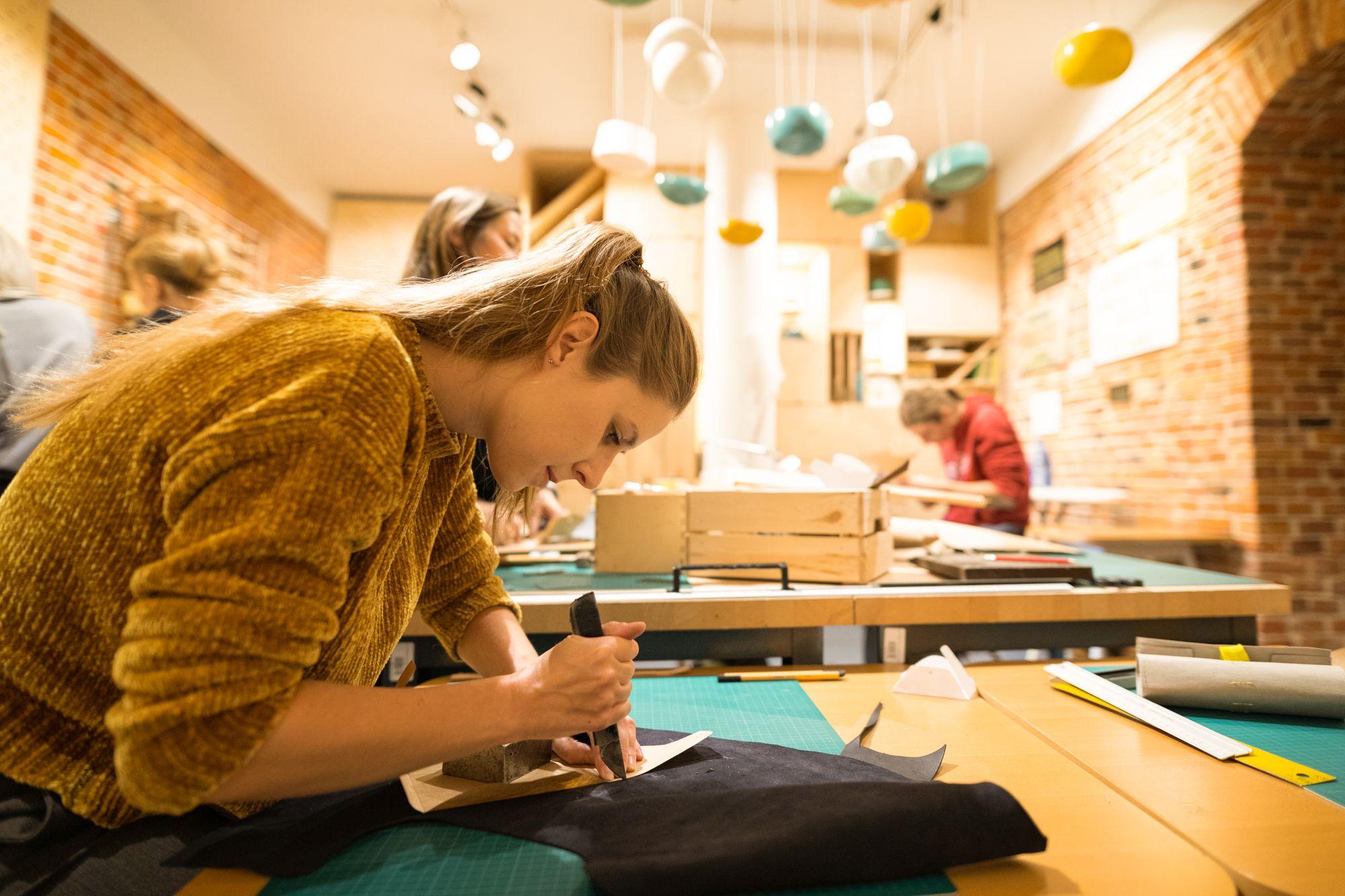 dziewczyna w trakcie pracy pochyla się nad blatem, w ręku ma narzędzia kaletnicze