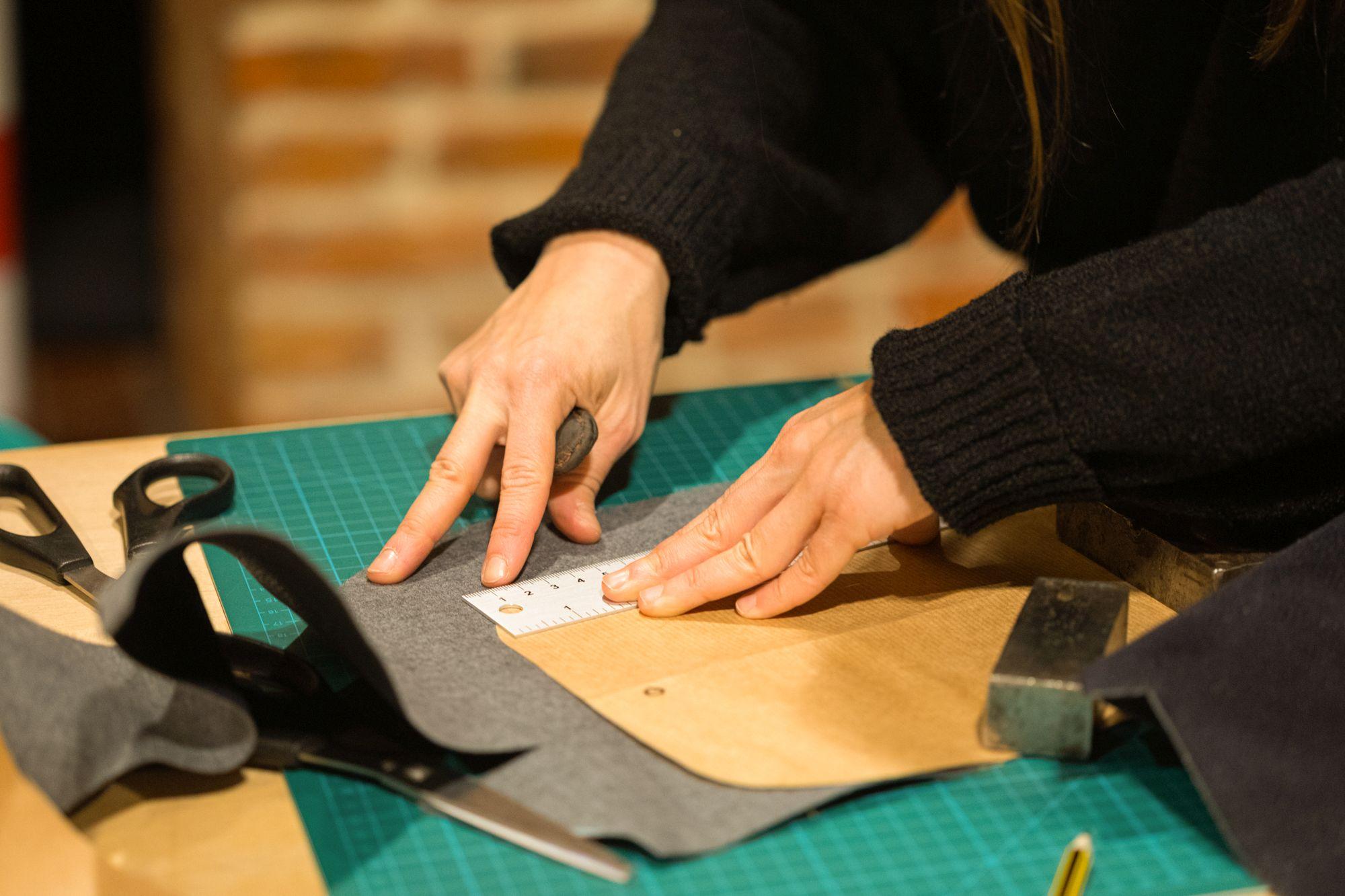 blat w pracowni kaletniczej, dłonie trzymają materiały skórzane