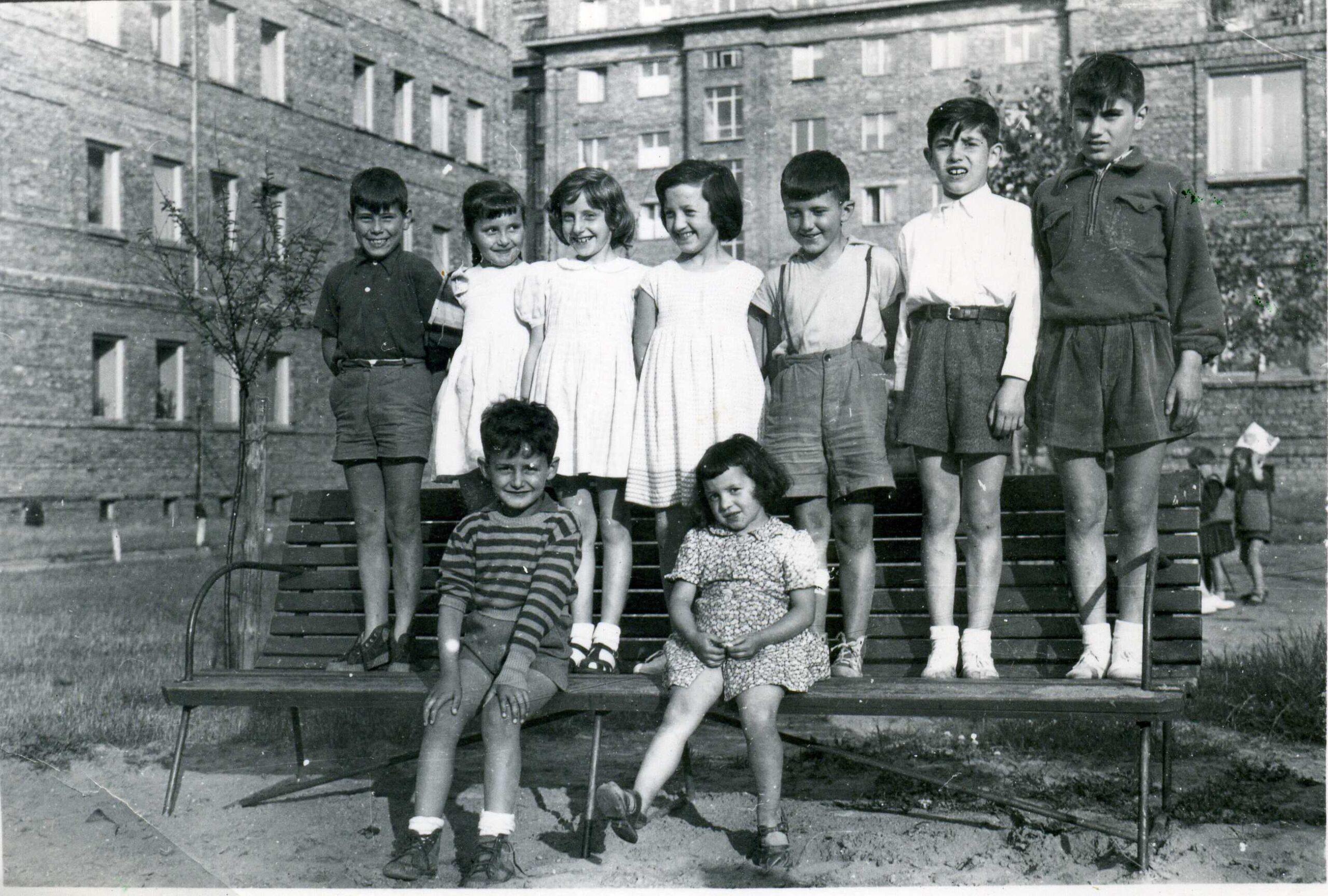 dwoje dzieci siedzi na ławce, siedmioro za nimi stoi, w tle kamienice
